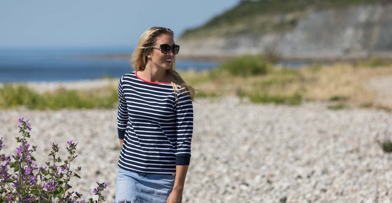 Lady on pebble beach next to purple flowers  wearing a striped navy Breton