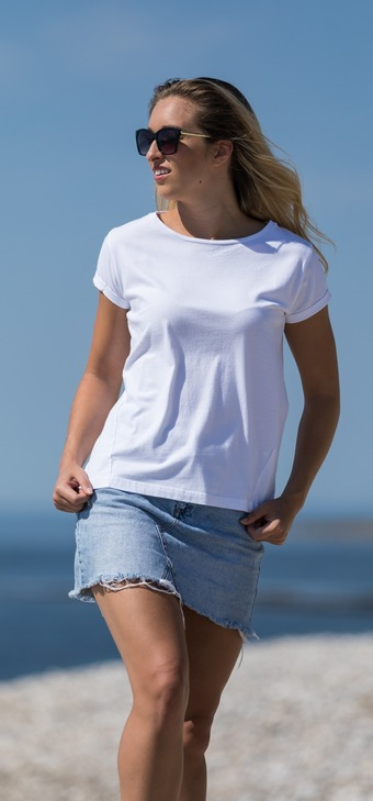 Lady with sunglasses wearing denim skirt & white Janey  T shirt stood on pebble beach