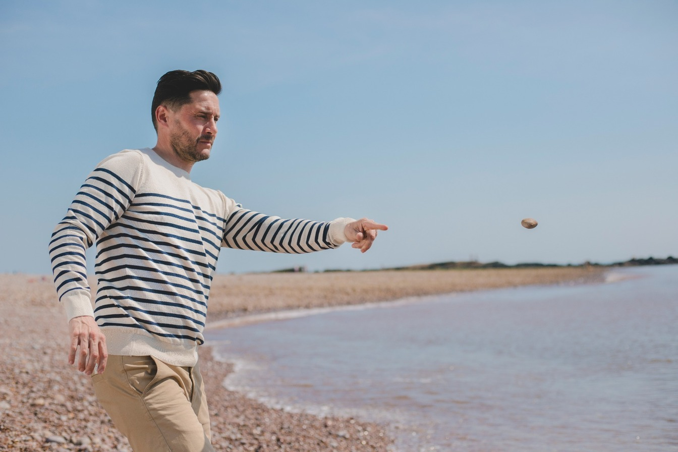 Man on pebble beach wearing a regenerated jumper throwing stone into sea