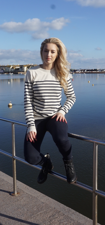 Young lady wearing jeans & Ren striped  jumper sat on railing by sea