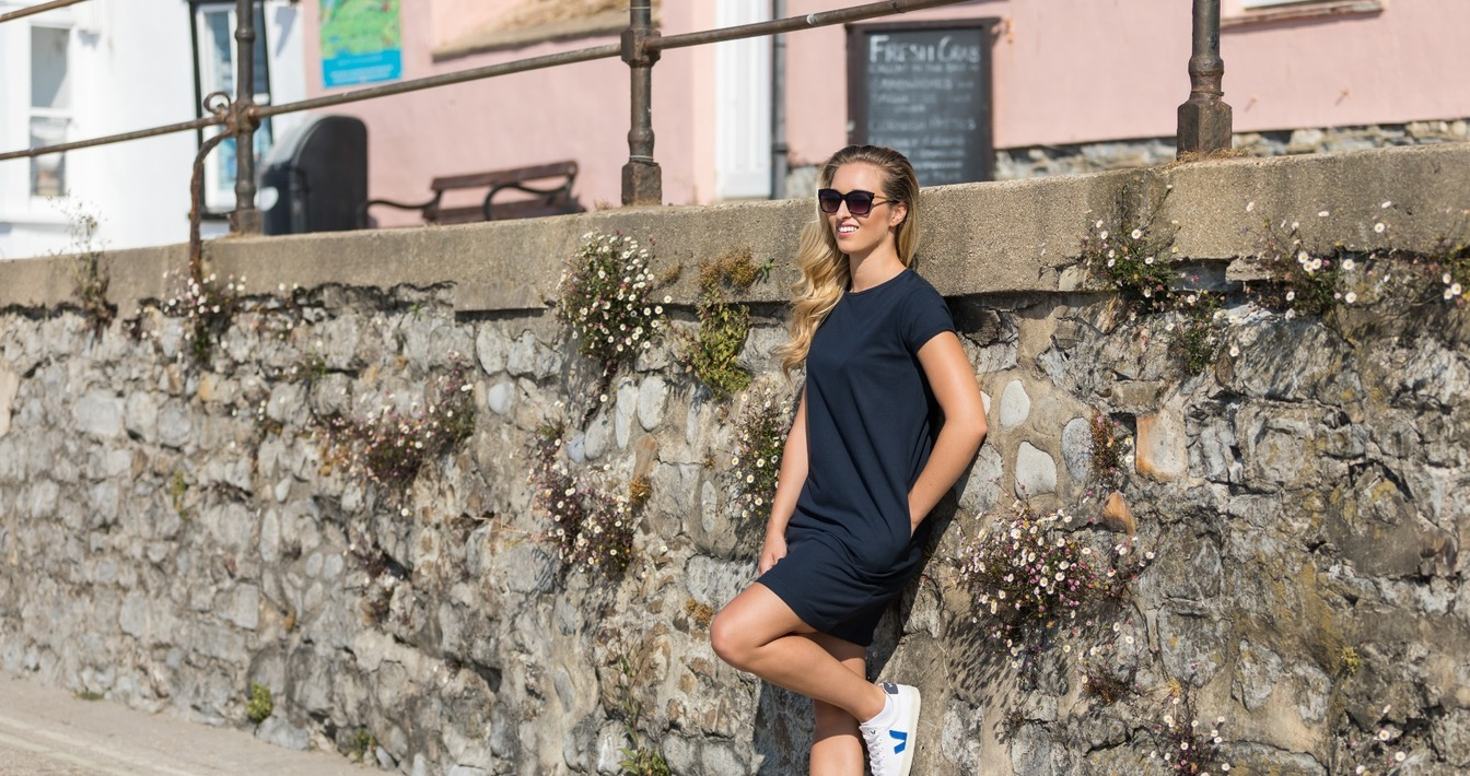 Young lady wearing Navy pocket dress & sunglasses leaning against stone wall