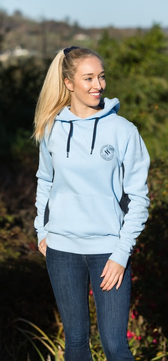 Young lady wearing sky blue hoodie & shorts leaning on wall by sea